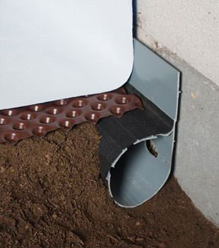 Closeup of a crawl space drainage system installed in Edina