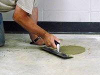 Repairing the cored holes in the concrete slab floor with fresh concrete and cleaning up the Rushville home.