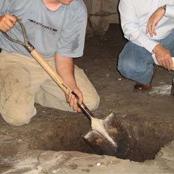 Digging a hole for the engineered fill used in a crawl space support system installation in Palmyra