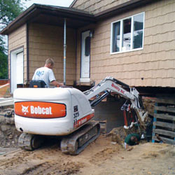 Excavating to expose the foundation walls and footings for a replacement job in Carthage