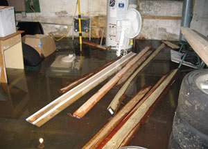 A severely flooding basement in Rushville, with lumber and personal items floating in a foot of water